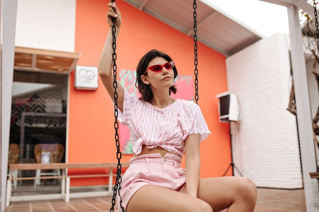 Ładna kobieta siedzi na huśtawce w okularach przeciwsłonecznych. odkryty strzał opalony kaukaski dama w t-shirt na tle miasta.