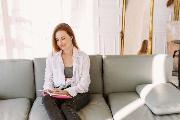 Ładna kobieta siedzi na kanapie w domu i pisze w zeszycie na swoim laptopie
