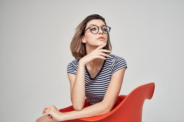 Ładna kobieta siedzi na krześle moda ubrania jasne tło