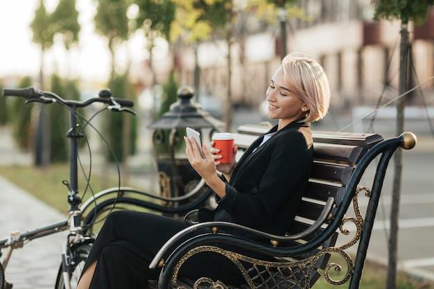 Ładna kobieta siedzi na ławce