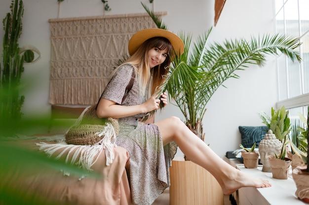 Ładna kobieta siedzi na łóżku w swoim mieszkaniu boho