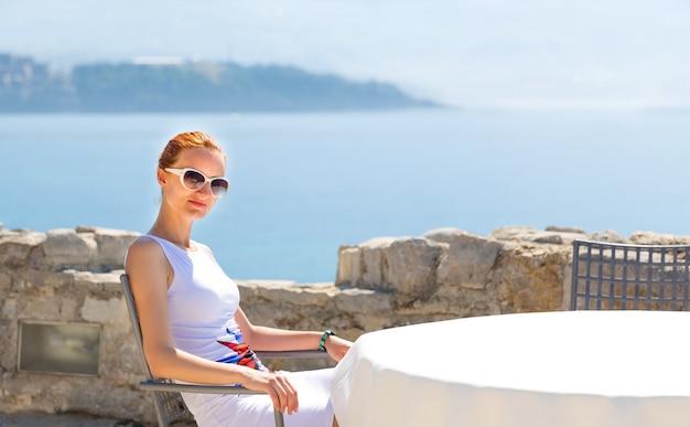 Ładna kobieta siedzi na tarasie z widokiem na morze luksusowego hotelu czarnogóry z widokiem na góry