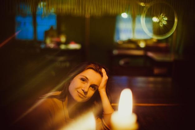 Ładna kobieta siedzi przy barem w restauraci