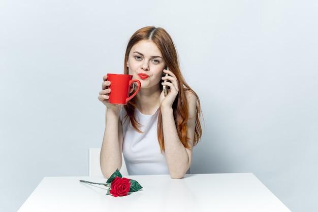Ładna kobieta siedzi przy stole z czerwonym kwiatem róży i rozmawia przez telefon