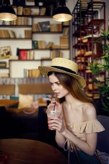 Ładna kobieta siedzi przy stole z drinkiem w komunikacji w kawiarni