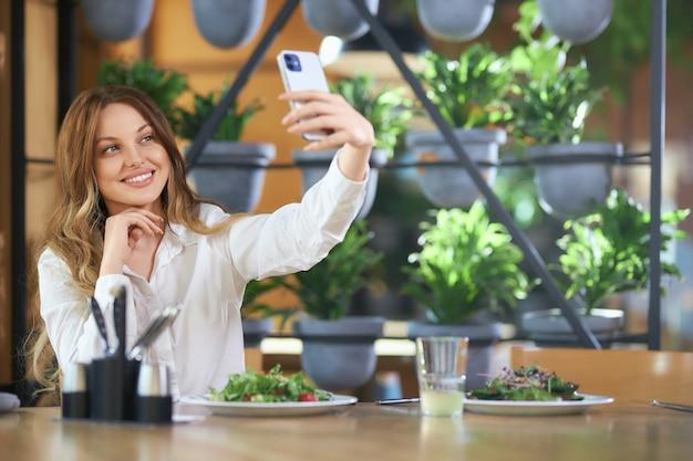 Ładna kobieta siedzi w kawiarni i robi selfie