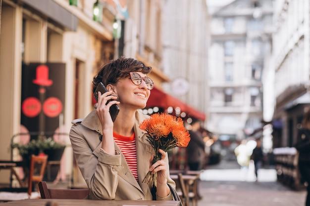 Ładna kobieta siedzi w kawiarni w chińskim mieście i rozmawia przez telefon