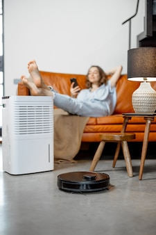 Ładna kobieta siedzi w pobliżu oczyszczacza powietrza i urządzenia nawilżającego w pobliżu kanapy monitorującej jakość powietrza w telefonie podczas czyszczenia podłogi. pojęcie mikroklimatu zdrowia w domu.