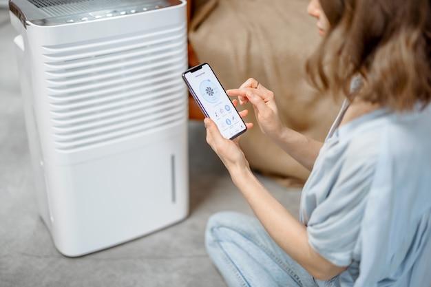 Ładna kobieta siedzi w pobliżu urządzenia oczyszczającego powietrze i nawilżającego w pobliżu kanapy monitorowania jakości powietrza w smartfonie. pojęcie mikroklimatu zdrowia w domu.