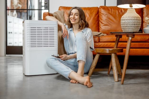 Ładna kobieta siedzi w pobliżu urządzenia oczyszczającego powietrze i nawilżającego w pobliżu kanapy monitorującej jakość powietrza w telefonie. pojęcie mikroklimatu zdrowia w domu. patrząc na aparat.