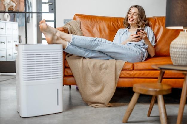 Ładna kobieta siedzi w pobliżu urządzenia oczyszczającego powietrze i nawilżającego w pobliżu kanapy monitorującej jakość powietrza w telefonie. pojęcie mikroklimatu zdrowia w domu.