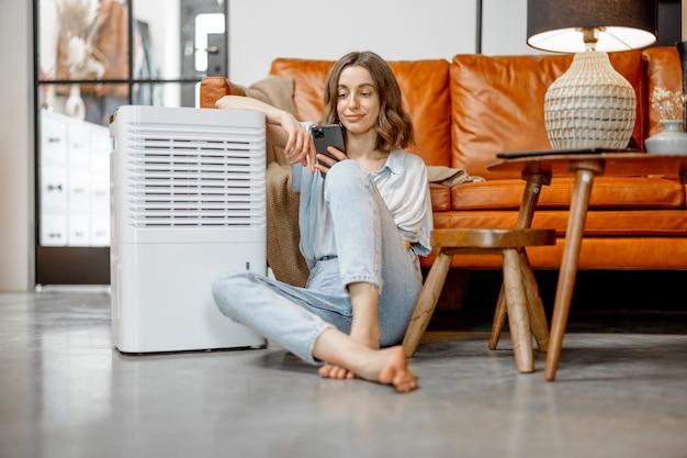 Ładna kobieta siedzi w pobliżu urządzenia oczyszczającego powietrze i nawilżającego w pobliżu kanapy za pomocą smartfona. pojęcie mikroklimatu zdrowia w domu.