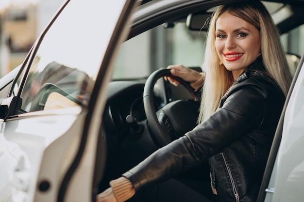 Ładna kobieta siedzi w swoim samochodzie