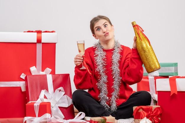 Ładna kobieta siedzi wokół prezentów świątecznych obchodzi z szampanem na białym tle