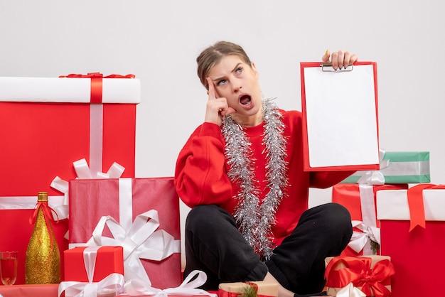 Ładna kobieta siedzi wokół prezentów świątecznych z notatką na białym tle