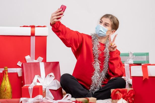 Ładna kobieta siedzi wokół świątecznych prezentów, biorąc selfie na białym tle