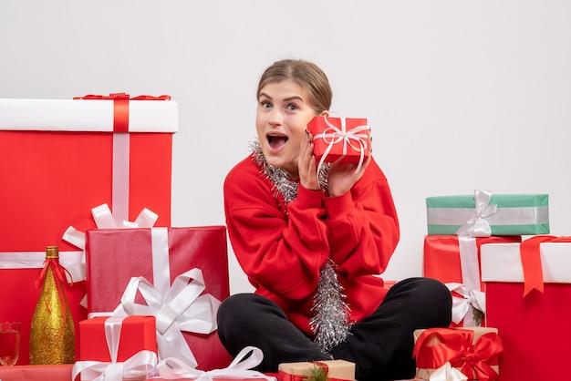 Ładna kobieta siedzi wokół świątecznych prezentów na białym tle