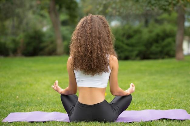 Ładna kobieta siedzi z powrotem robi joga medytacji
