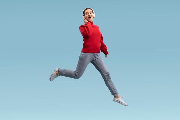 Ładna kobieta skoki na białym tle na niebiesko