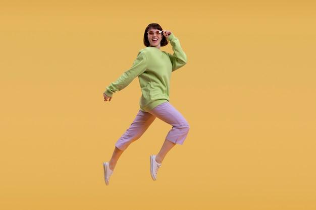Ładna kobieta skoki na białym tle na pomarańczowy