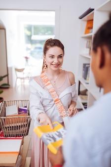Ładna kobieta. śliczna brunetka z uśmiechem na twarzy podczas robienia książki