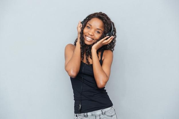 Ładna kobieta słucha muzyki w słuchawkach na szarej ścianie