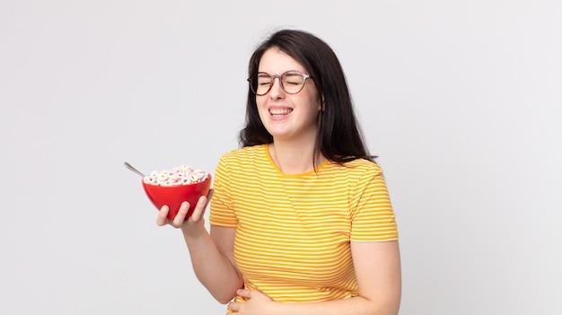 Ładna kobieta śmiejąca się głośno z jakiegoś przezabawnego żartu i trzymająca miskę ze śniadaniem