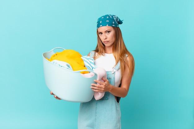 Ładna kobieta, smutna i jęcząca z nieszczęśliwym spojrzeniem i płacząca, trzymająca kosz do prania