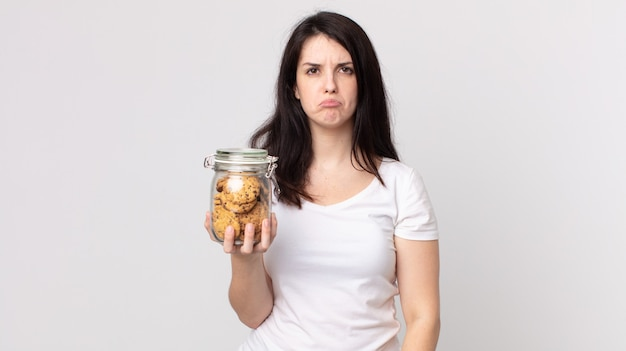Ładna kobieta smutna i jęcząca z nieszczęśliwym spojrzeniem, płacząca i trzymająca szklaną butelkę po ciastkach