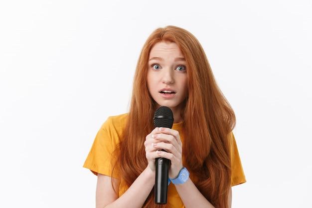 Ładna kobieta śpiewa z dezorientacją i zmartwieniem wyrazu twarzy.