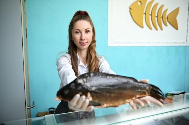 Ładna kobieta sprzedawca ryb za ladą, trzymając w wyciągniętych rękach ogromną rybę. sprzedaż detaliczna owoców morza w sklepie rybnym