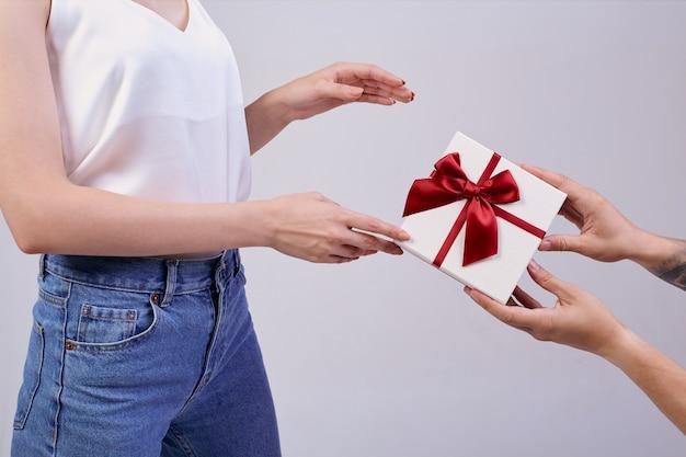 Ładna kobieta stoi na szaro w okularach pc i białej koszulce. minuta szczęścia. ręce kogoś innego dają prezent, kobieta jest zaskoczona.