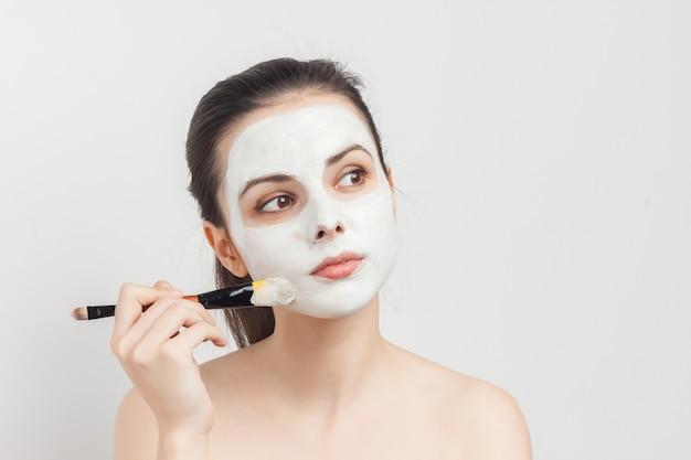 Ładna kobieta, stosując krem do pędzla na odmładzanie pielęgnacji skóry twarzy