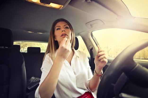 Ładna kobieta stosuje tusz do rzęs w samochodzie