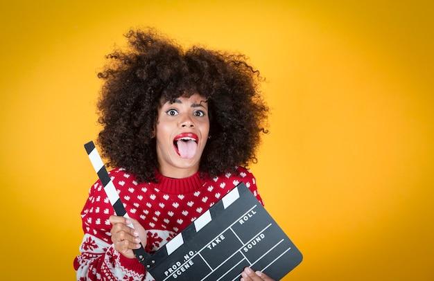 Ładna kobieta, świąteczny klaps filmowy, niespodzianka na żółtym tle