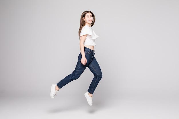 Ładna kobieta świętuje skacząc i wiwatując na białym tle na białej ścianie