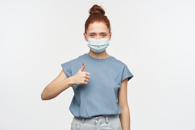 Ładna kobieta, szczęśliwa dziewczyna o rudych włosach zebranych w kok. ubrana w niebieską koszulkę, dżinsy i ochronną maskę na twarz. pokazuje kciuk do góry. pojedynczo na białej ścianie