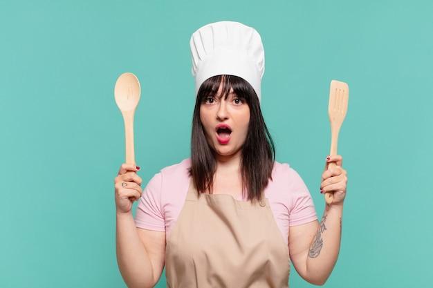 Ładna kobieta szefa kuchni przestraszona ekspresja
