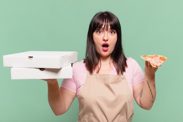 Ładna kobieta szefa kuchni przestraszona wyrazem twarzy i trzymająca pizzę