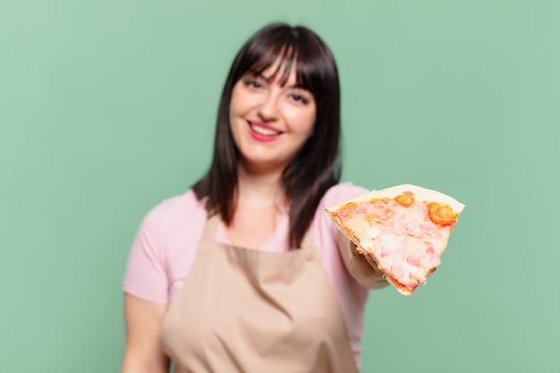 Ładna kobieta szefa kuchni szczęśliwa ekspresja i trzymająca pizzę
