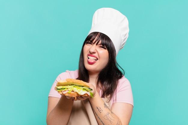 Ładna kobieta szefa kuchni zły wyraz twarzy i trzymająca kanapkę