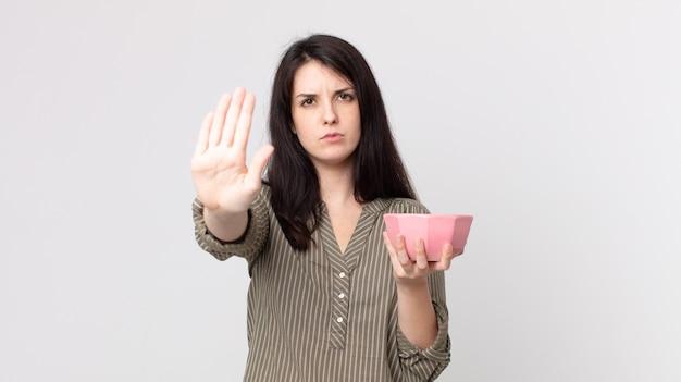 Ładna kobieta szuka poważnego wyświetlono otwartej dłoni, co gest zatrzymania, trzymając pustą miskę garnka. asystent agenta z zestawem słuchawkowym