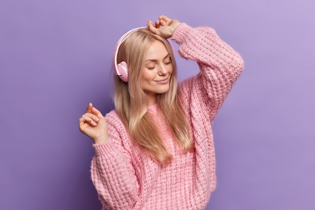 Ładna kobieta tańczy beztrosko, cieszy się każdą melodią, słucha muzyki w słuchawkach, zamknięte oczy