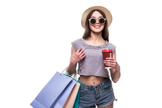 Ładna kobieta torby na zakupy i trzymając kubek papierowy kawy na białym tle