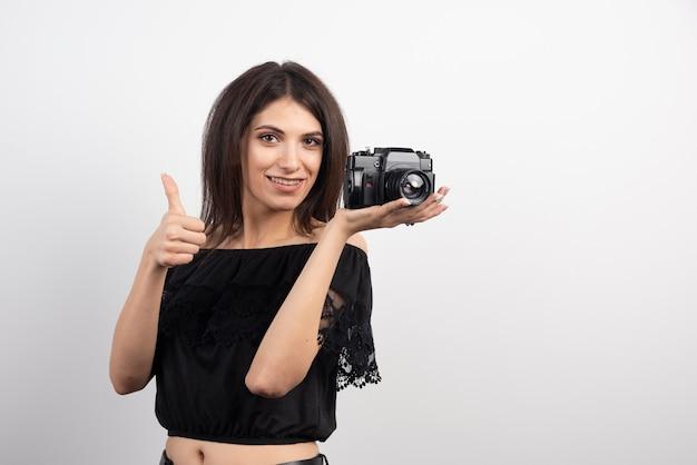 Ładna kobieta trzyma aparat i daje kciuki do góry.