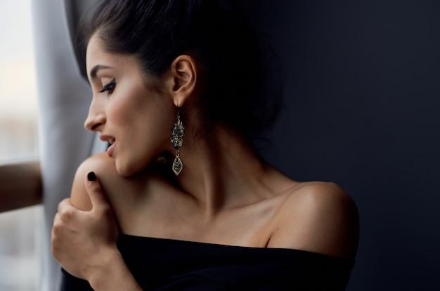 Ładna kobieta trzyma aparat w pobliżu elegancki styl moda ozdoba okna. zdjęcie wysokiej jakości