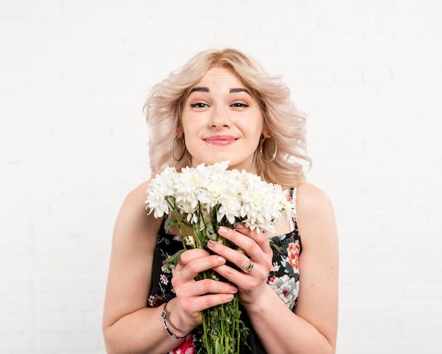 Ładna kobieta trzyma białe kwiaty patrzeje kamerę
