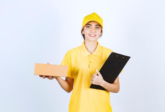 Ładna kobieta trzyma brązowe puste pudełko papierowe rzemieślnicze z folderem.