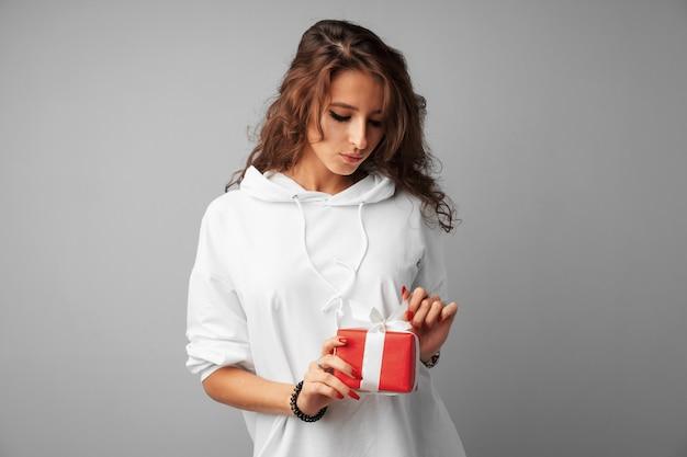 Ładna kobieta trzyma czerwone pudełko w dłoniach