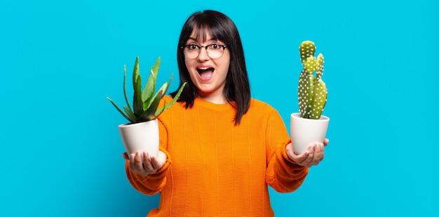 Ładna kobieta trzyma garnki kaktusów